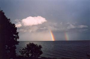 Grey lake scape with with cloud and rainbow