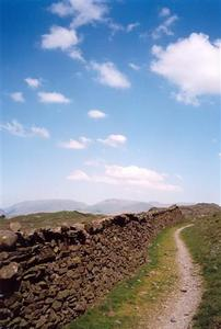 Stone wall and path on top of hill, blue sky with a few light clouds