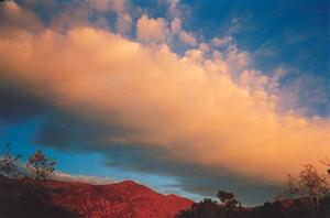 Orange cloud on blue sky, red mountains