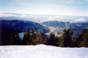 View of plains and small hills below snow covered hill