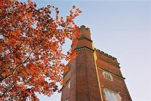 Brick red Brockwood Tower beside red autumn leaves